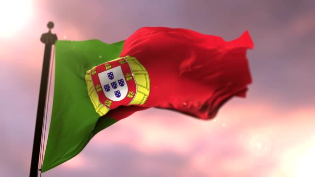 Flag of Portugal waving at wind in slow at sunset, loop video