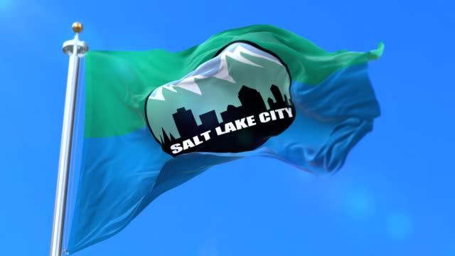 vidéos et rushes de drapeau de la ville de salt lake city, ville de l'utah aux états-unis d'amérique - boucle - lac salé