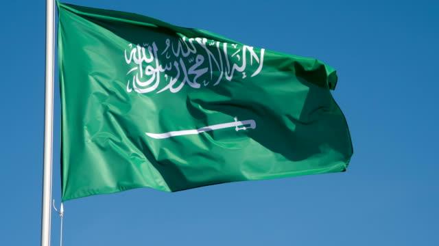 stockvideo's en b-roll-footage met vlag van saoedi-arabië verlicht door de zon - riyad