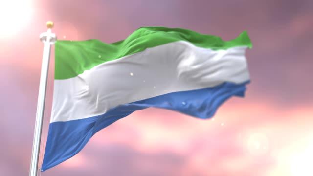flag of sierra leone waving at wind in slow at sunset, loop - sierra leone video stock e b–roll