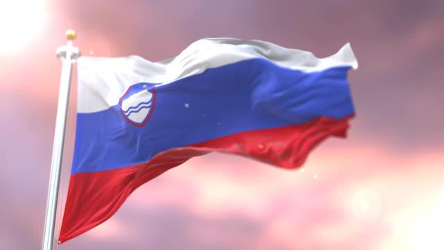 yavaş günbatımı, döngü içinde slovenya sallayarak bayrak rüzgar - styria stok videoları ve detay görüntü çekimi