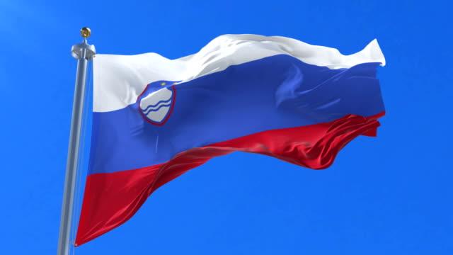 flag of slovenia waving at wind in slow in blue sky, loop - styria filmów i materiałów b-roll