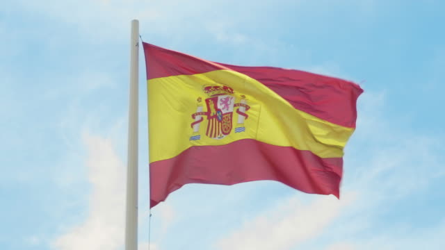 Flag of Spain. Red and yellow Spanish flag waving in the wind on a flagpole against the clear blue sky