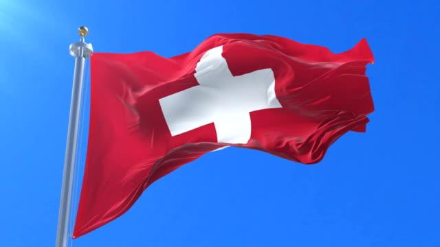 Flag of Switzerland waving at wind in slow in blue sky, loop video