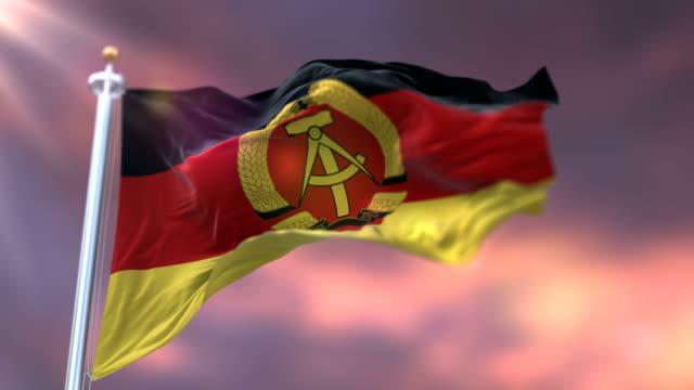 vídeos de stock e filmes b-roll de flag of the german democratic republic or east germany waving at sunset. loop - berlin wall