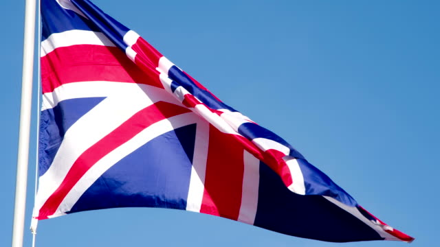 Flag of the Great Britain Lit by the Sun The Big State Flag is illuminated by the sun and flutters epically in the wind against the blue sky. Slow Motion 240 fps royalty stock videos & royalty-free footage