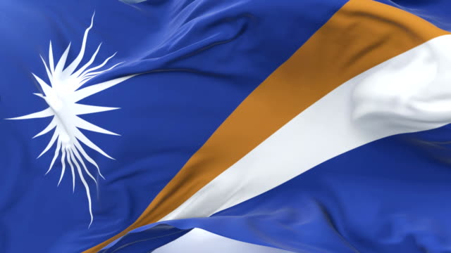 flag of the marshall islands waving at wind in slow with blue sky, loop - majuro video stock e b–roll
