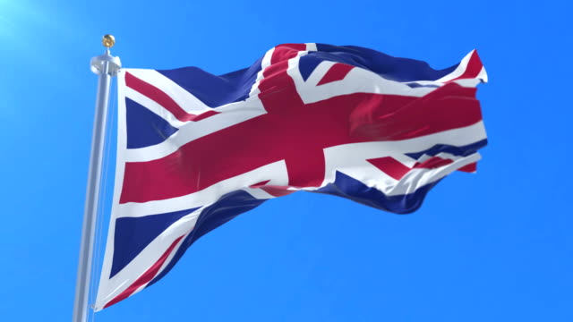 Flag of the United Kingdom waving at wind with blue sky, loop video