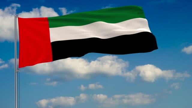 flag of united arab emirates against background of clouds floating on the blue sky - uae flag filmów i materiałów b-roll