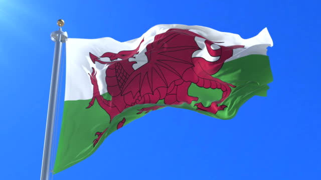 Flag of Wales waving at wind in slow with blue sky, loop video