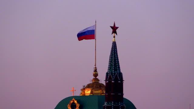 flag over the grand kremlin palace. star on the tower. evening. - kreml bildbanksvideor och videomaterial från bakom kulisserna