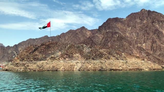 flaga zea macha na szczycie wzgórza w środku jeziora hatta na niebieskim, pochmurnym tle nieba - uae flag filmów i materiałów b-roll
