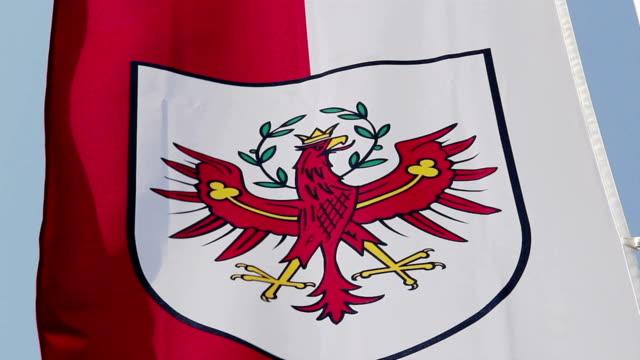 bandiera con tirolo blasone di a vento - stato federato del tirolo video stock e b–roll