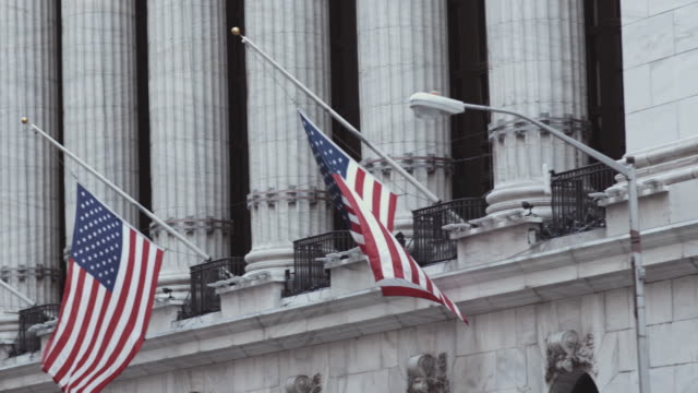 Flags above the New York Stock Exchange. American National Flags blow gently in front of the marble of New York's Stock Exchange on Wall Street. financial building stock videos & royalty-free footage