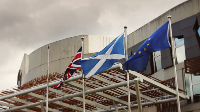 Flags at Scottish Parliament Building The Scottish, UK and EU flags flap and unfurl in the wind outside the Scottish Parliament Building. scotland stock videos & royalty-free footage