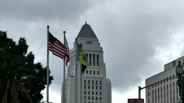 fahnen wehen vor dem los angeles city hall building - establishing shot stock-videos und b-roll-filmmaterial