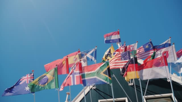 Flags of different states of the world are fluttering in the wind at the roof of an old wooden house Flags of many countries in an old wooden house. The bottom view of shooting against the blue sky. 4K video international match stock videos & royalty-free footage