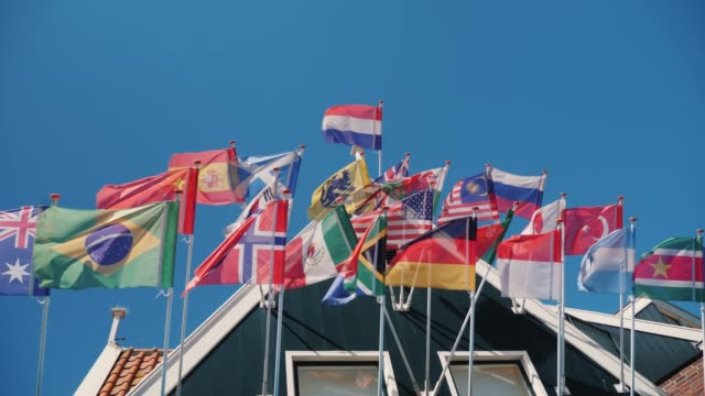 Flags of many countries in an old wooden house. The bottom view of shooting against the blue sky Flags of many countries in an old wooden house. The bottom view of shooting against the blue sky. 4K video international match stock videos & royalty-free footage
