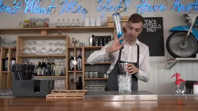 Flair bartending. A handsome young bartender pours a blue curacao liquor into a glass with ice cubes. video