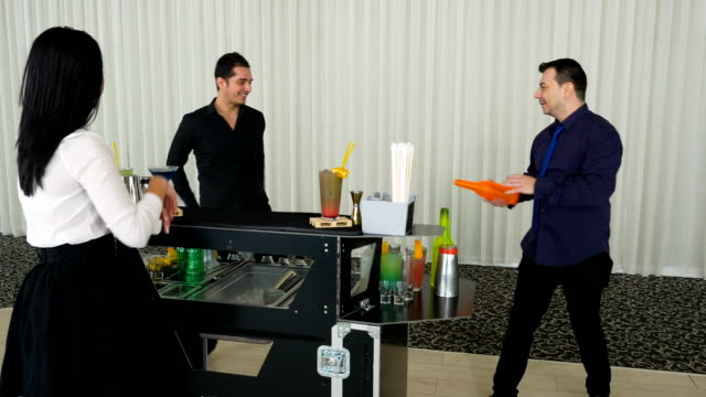 Flair bartending performed by two bartenders and a woman watching by the bar video