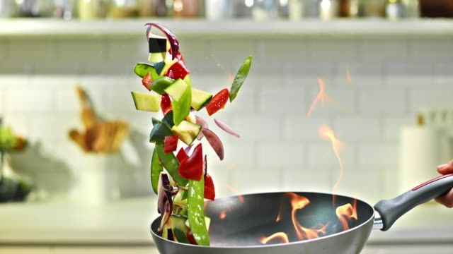 SLO MO TU Flambaying colorful vegetables Slow motion tilt up medium shot of vegetables being flambayed and shaken into the air in a nice modern kitchen. cooking pan stock videos & royalty-free footage
