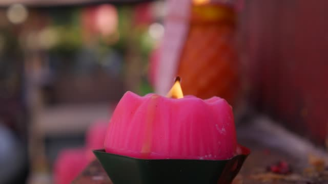 vídeos de stock e filmes b-roll de flame from burning pink candles in taoist temple during the celebration of chinese new year. 4k - hinduísmo