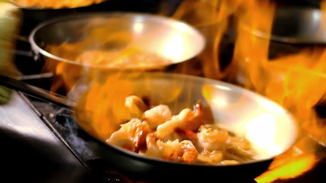 エビで満たされたフライパンの下で炎が燃える。 - 料理人点の映像素材/bロール
