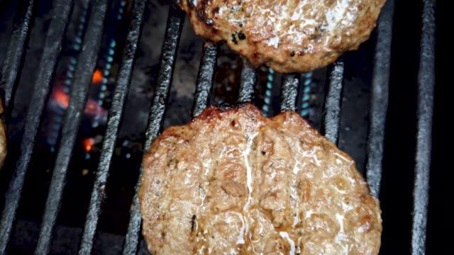 flames char saftig, lecker, lecker, rindfleisch-burger auf einem heißen grill rost langsam schwenken nahaufnahme. - niedrig stock-videos und b-roll-filmmaterial