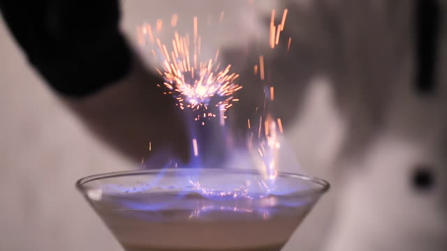 Flames in Cocktail Glass in Slow Motion, Burning Cinnamon in Alcohol Drink, Barman Makes Drink. Beautiful Sparkling Effect