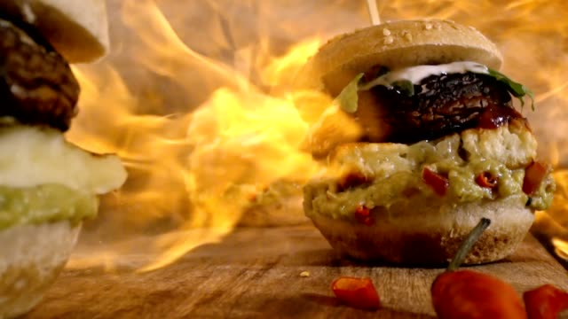 Flames over Veggie Burger with Grilled Cheese, Mushroom, Guacamole and Arugula in Slow Motion video