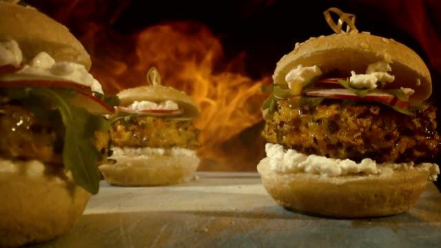 キノアパティ、カッテージチーズ、ラディッシュ、ルッコラと野菜バーガーの炎 - ベジタリアン料理点の映像素材/bロール