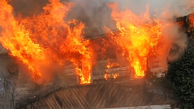 flames shooting from second story window at house fire - incendio video stock e b–roll