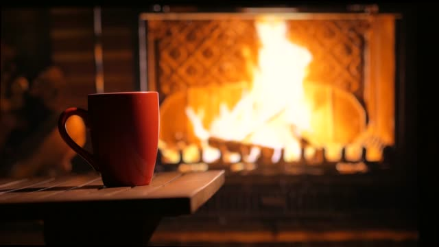 A flaming fireplace and a cup of tea. Home mood. Background A flaming fireplace and a cup of tea. Home mood. Background fireplace stock videos & royalty-free footage