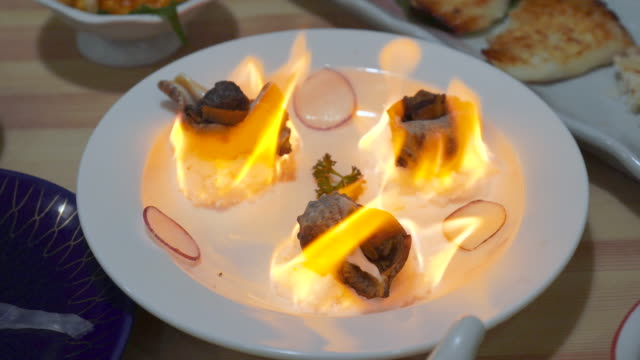 vídeos de stock e filmes b-roll de flaming snails served aflame at asian restaurant. - bugio