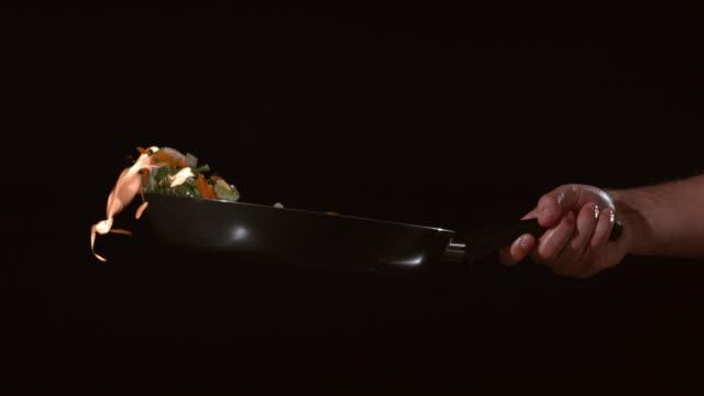 flaming stirfry i slow motion - frying pan bildbanksvideor och videomaterial från bakom kulisserna