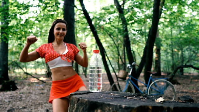flash mob. bottle cap challenge: you need to unscrew the bottle cap with a kick. the girl, using her feet, tries to unscrew the bottle. - coperchio video stock e b–roll