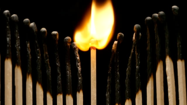 SLOW MOTION: Flash of single matchstick between row of burned matchsticks video