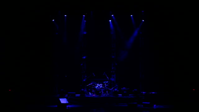 Flashing blue spotlights that illuminate the stage at a concert with a drum set
