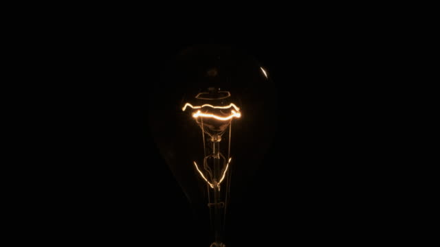 Flashing spiral of an old bulb. Tungsten filament on a black background.