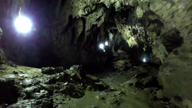 flashlight and human shadow in polovragi cave,romania - кейвинг стоковые видео и кадры b-roll