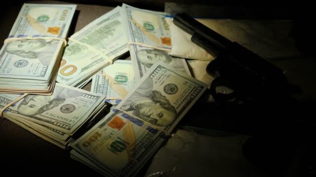 en ficklampa stråle lyser en cache av vapen och droger. brottslighet och olaglig aktivitet koncept - dirty money bildbanksvideor och videomaterial från bakom kulisserna