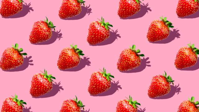vídeos de stock e filmes b-roll de flat lay composition with strawberry berry on pink background - padrão repetido