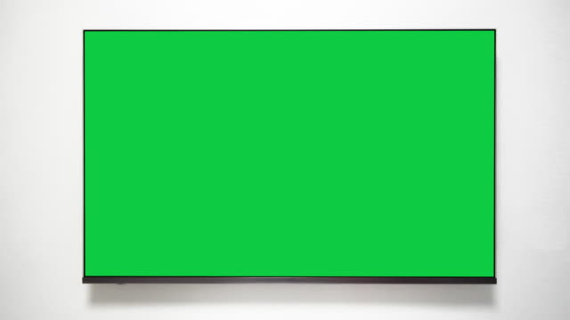 4K - Flat screen TV with green screen. Chroma key TV on white wall