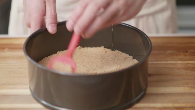 flating butter crushed bicuits for the base of cheese cake - sernik filmów i materiałów b-roll
