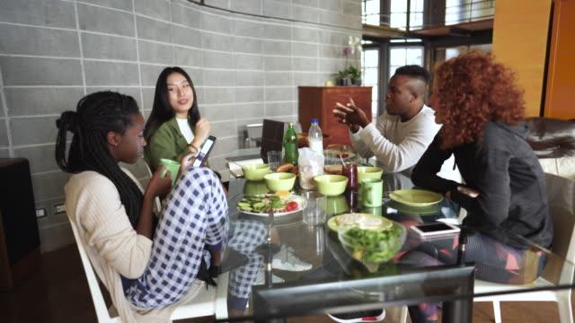 vídeos de stock, filmes e b-roll de flatmates que comem o pequeno almoço na tabela de cozinha do apartamento - vegetarian meal