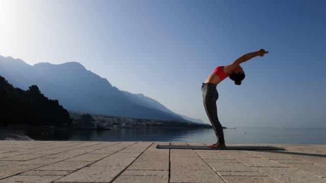 Flexible girl practicing yoga in scenic seascape