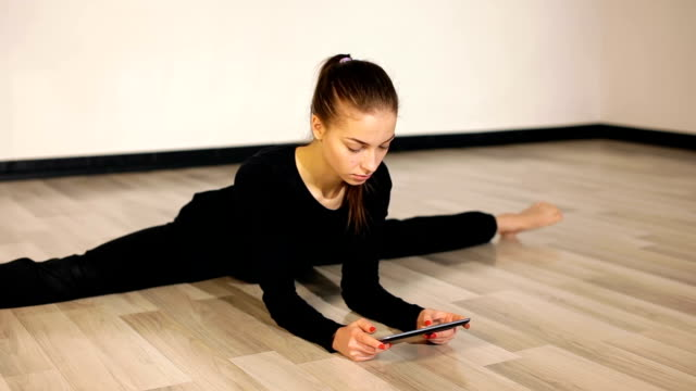 Flexible girl sitting on splits and reat tablet pc video