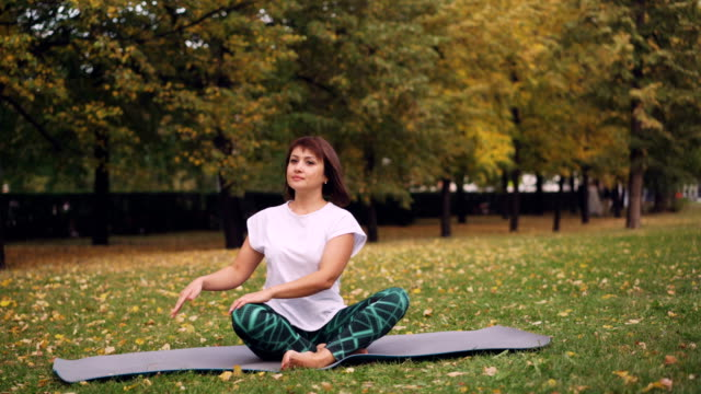 Flexible girl yogini is practising simple twist pose then resting in lotus position sitting on yoga mat on grass in park. Recreational area and people concept.