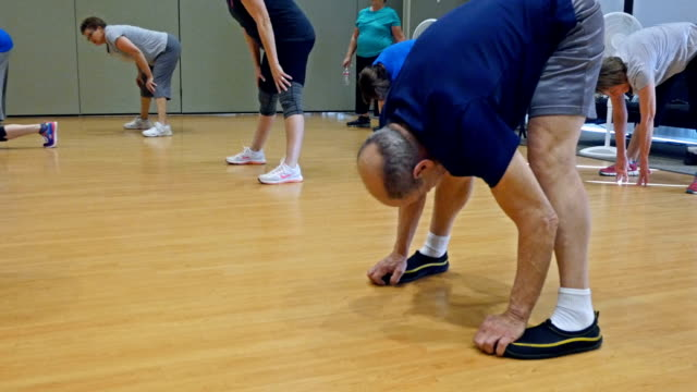 Flexible senior man stretches in exercise class video