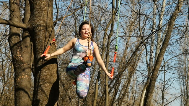 Flexible woman makes the aerogravity exercises on ropes Young woman practicing aerogravity in the park. The woman makes physical exercises on the ropes on tree. Flexible female hanging on the ropes and stretching her body and muscles. She's moving slowly and accuracy. arthropod stock videos & royalty-free footage